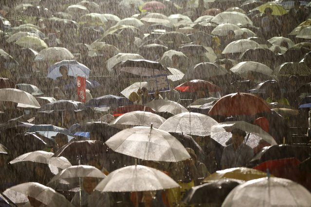 Protesters holding umbrellas gather at a rally against Japan's Prime Minister Shinzo Abe's security bill and his administration, during heavy rain caused by typhoon Etau, in Tokyo September 9, 2015. (Photo by Issei Kato/Reuters)