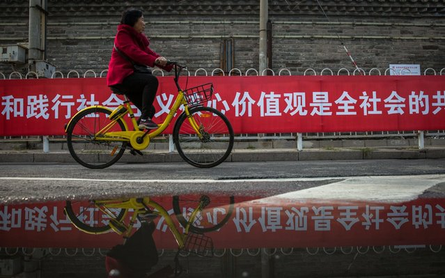 """A Chinese woman rides a bicycle past a banner showing propaganda for 19th National Congress of the Communist Party of China (CPC) with words """"It is the common responsibility of the whole society to cultivate and practice core socialist values"""", in Beijing, China, 20 October 2017. China holds the 19th Congress of the Communist Party of China, the country's most important political event where the party's leadership is chosen and plans are made for the next five years. Xi Jinping is expected to remain as the General Secretary of the Communist Party of China for another five-year term. (Photo by Roman Pilipey/EPA/EFE)"""