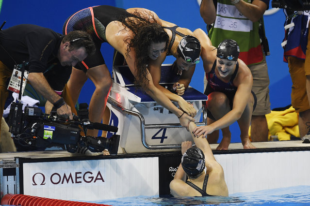 Katie Ledecky of the United States is greeted by teammates (from left) Allison Schmitt, Madeline Dirado and Leah Smith after anchoring them to a come-from-behind win during the women's 4x 200-meter freestyle relay final at Rio 2016 on Wednesday, August 10, 2016. The United States edged out Australia (silver) and Canada (bronze). Missy Franklin was not added to the foursome after she struggled during an individual freestyle semifinal. (Photo by Aaron Ontiveroz/The Denver Post)