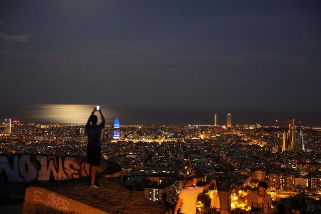 A man wearing a protective mask takes a picture of the city of Barcelona, as the spread of the coronavirus disease (COVID-19) continues, in Barcelona, Spain on May 6, 2020. (Photo by Nacho Doce/Reuters)