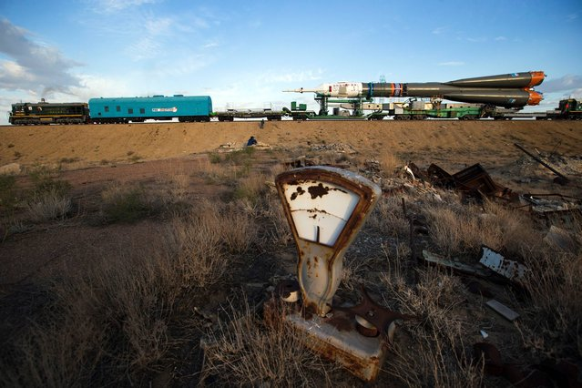 An old tossed out scales is scattered in a field as Russia's Soyuz-FG booster rocket with the space capsule Soyuz TMA-14M that will carry a new crew to the International Space Station (ISS) is transported from hangar to the launch pad at the Russian leased Baikonur Cosmodrome, Kazakhstan, Tuesday, September 23, 2014. (Photo by Pavel Golovkin/AP Photo)