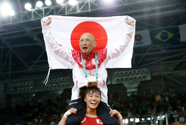 Japan's Eri Tosaka celebrates with her coach winning against Azerbaijan's Mariya Stadnyk in their women's 48kg freestyle final match on August 17, 2016, during the wrestling event of the Rio 2016 Olympic Games at the Carioca Arena 2 in Rio de Janeiro. (Photo by Jack Guez/AFP Photo)