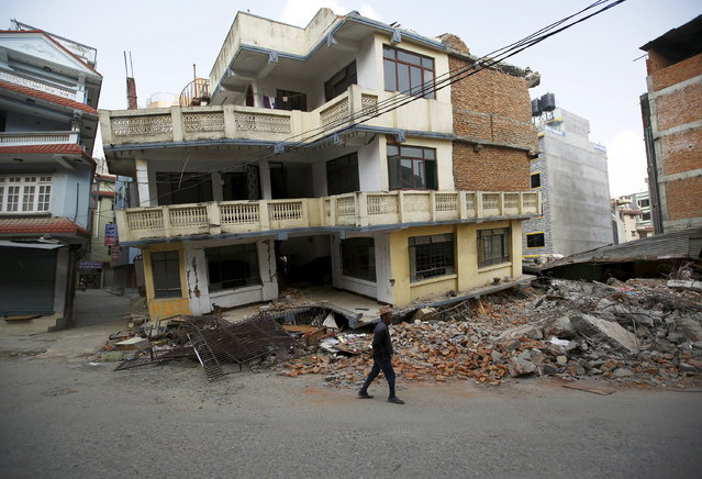 A man walks past a damaged and collapsed five-storey house, a month after the April 25 earthquake in Kathmandu, Nepal May 25, 2015. (Photo by Navesh Chitrakar/Reuters)