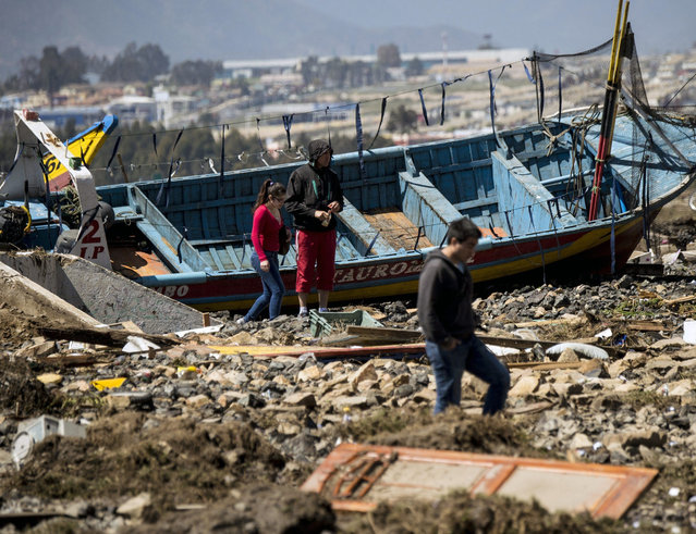 Residents walk between debris caused by the sea in the port of Coquimbo, some 445 km north of Santiago, during the eve's earthquake on September 17, 2015. (Photo by Martin Bernetti/AFP Photo)