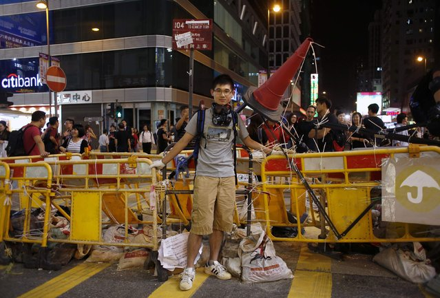 "Charky Leung, 24, an office worker, poses in front of a barricade at Mongkok shopping district in Hong Kong October 7, 2014. Leung who mans the barricade said, ""I carry a mask as I am afraid of being pepper sprayed by the police. Here in Mongkok we have a clear demand of a real universal suffrage, rather than just asking Hong Kong leader to step down"". (Photo by Bobby Yip/Reuters)"