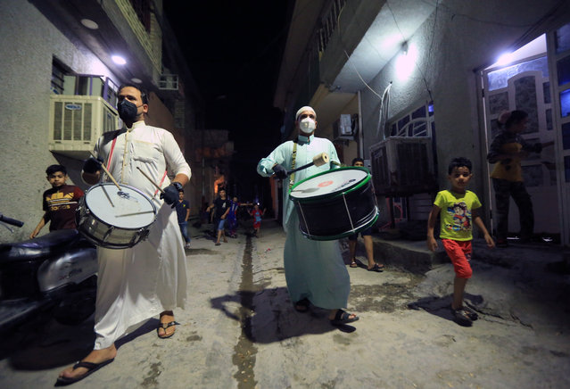 Muhammed Muhsin and Raid Kaabi wearing protective masks and gloves play drum to wake public up for sahur meal on a street during Ramadan, amid coronavirus (Covid -19) pandemic, in Baghdad, Iraq on May 4, 2020. Sahur meal is the last meal before a long day of fasting that starts with the call to prayer at sunrise on Ramadan month. (Photo by Murtadha Al-Sudani/Anadolu Agency via Getty Images)
