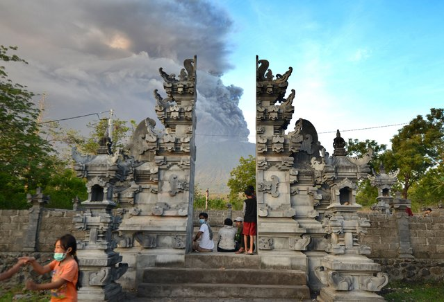 Balinese people look at Mount Agung during an eruption seen from Kubu sub-district in Karangasem Regency on Indonesia's resort island of Bali on November 26, 2017. Mount Agung belched smoke as high as 1,500 metres above its summit, sparking an exodus from settlements near the mountain. (Photo by Sonny Tumbelaka/AFP Photo)