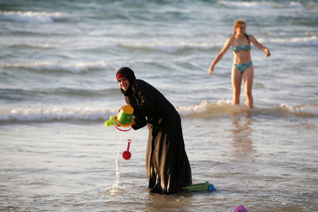 A Muslim woman wearing a Hijab stands in the waters in the Mediterranean Sea as an Israeli stands nearby on the beach in Tel Aviv, Israel August 21, 2016. (Photo by Baz Ratner/Reuters)