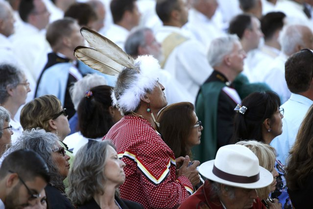 Members of the public watch as Pope Francis (not pictured) presides over a Canonization Mass for Friar Serra at the Basilica of the National Shrine of the Immaculate Conception in Washington September 23, 2015. (Photo by Kevin Lamarque/Reuters)