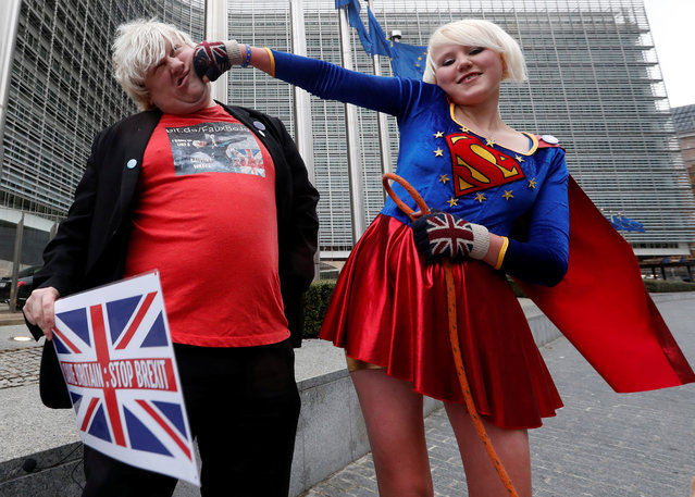 "Britain's anti-Brexit activists Madeleina Kay, who nicknamed herself as ""EU Supergirl"", and Drew Galdron, who is also an impersonator of British Foreign Secretary Secretary Boris Johnson, perform outside the European Commission headquarters in Brussels, Belgium December 8, 2017. (Photo by Yves Herman/Reuters)"