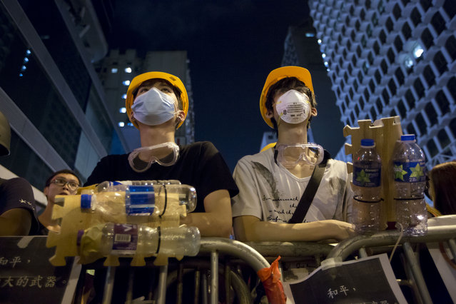 Protesters wear protective gear made by plastic bottle at a barricade in the Mong Kok district of Hong Kong, early Monday, October 20, 2014. Three weeks ago, students at a rally stormed a fenced-off courtyard outside Hong Kong's government headquarters, triggering unprecedented mass protests for greater democracy in the semiautonomous Chinese city. (Photo by Kin Cheung/AP Photo)