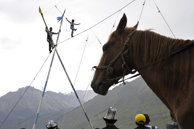 In this photo taken on Sunday, September 4, 2016, a boy performs a tight-rope walk during the second World Nomad Games at Issyk Kul lake in Cholpon-Ata, Kyrgyzstan. (Photo by Vladimir Voronin/AP Photo)