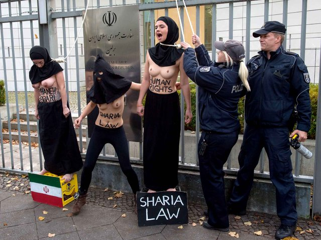 Topless Femen activists protest in front of the Iranian embassy against the execution of Reyhaneh Jabbari on October 27, 2014 in Berlin, Germany. (Photo by Marcus Golejewski/AFP Photo/Geisler-Fotopress/Picture-Alliance)
