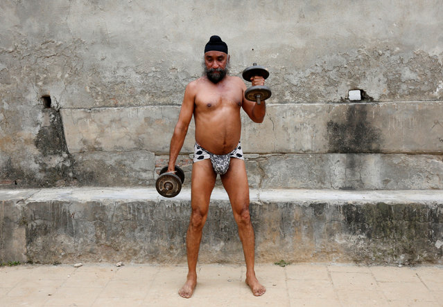 """A man uses dumbbells during a practice session at a traditional wrestling training centre called """"Akhaara"""" in Jammu March 31, 2017. (Photo by Mukesh Gupta/Reuters)"""