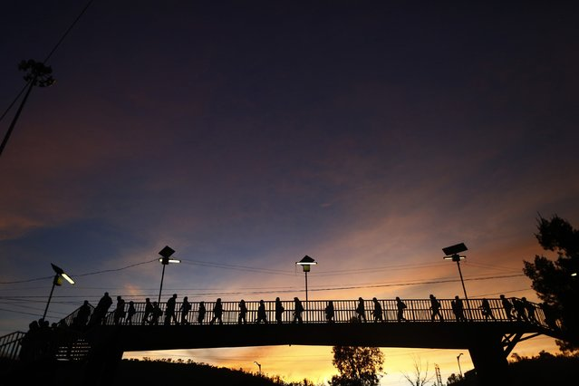 People cross a bridge before entering Indios Verdes Metro station in Mexico City, October 24, 2014. (Photo by Edgard Garrido/Reuters)