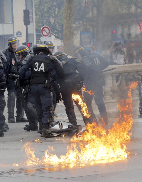 A riot police officer is evacuated by his colleagues after suffering burns from a petrol bomb thrown by leftist protesters during clashes in Paris, France, Thursday, September 15, 2016. (Photo by Christophe Ena/AP Photo)