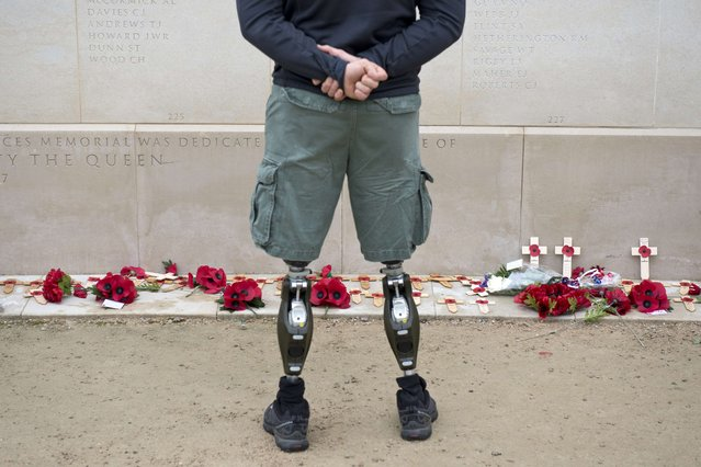 A member of the armed forces with prosthetic legs pays his respects at the Armed Forces Memorial in the National Memorial Arboretum on Armistice Day near Lichfield, Staffordshire, central England, on November 11, 2014. In services around the country tributes were paid to the millions of British servicemen and women who have died in conflict since the start of the First World War 100 years ago. (Photo by Oli Scarff/AFP Photo)