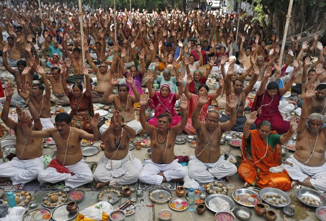 "Hindus raise their hands as they perform prayers on the holy day of ""Mahalaya"" in Ahmedabad, India, October 12, 2015. Hindus offer prayers with holy water after taking a dip in the river to honour the souls of their departed ancestors during Mahalaya, which is also called Pitru Paksha. (Photo by Amit Dave/Reuters)"