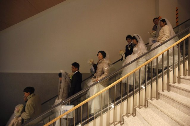 Newlyweds descend the escalator during a mass wedding ceremony of the Unification Church at Cheongshim Peace World Centre in Gapyeong, about 60 km (37 miles) northeast of Seoul February 17, 2013. The Unification Church founded by evangelist reverend Moon Sun-myung in Seoul in 1954, performed its first mass wedding in 1961 with 33 couples. Approximately 3,500 couples attended the mass wedding on Sunday. (Photo by Kim Hong-Ji/Reuters)