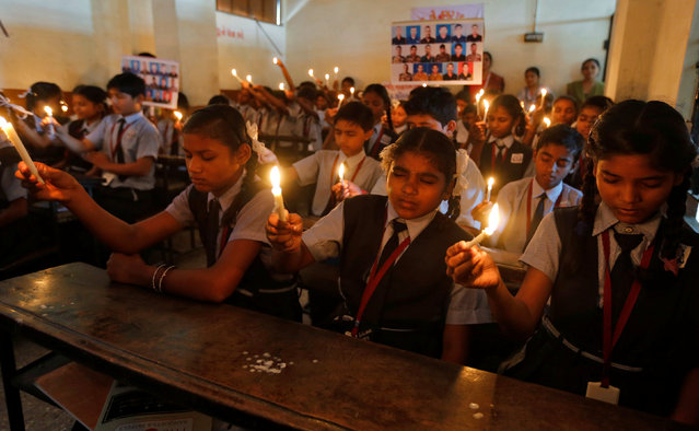 School girls hold candles during a vigil for the soldiers who were killed in Sunday's attack at an Indian army base in Kashmir's Uri, in Ahmedabad, India, September 20, 2016. (Photo by Amit Dave/Reuters)