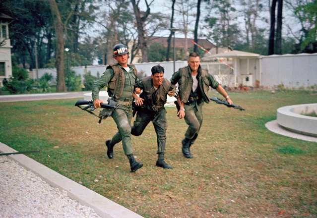 Two U.S. military policemen aid a wounded fellow MP during fighting in the U.S. Embassy compound in Saigon, January 31, 1968, at the beginning of the Tet Offensive. A Viet Cong suicide squad seized control of part of the compound and held it for about six hours before they were killed or captured. (Photo by AP Photo)