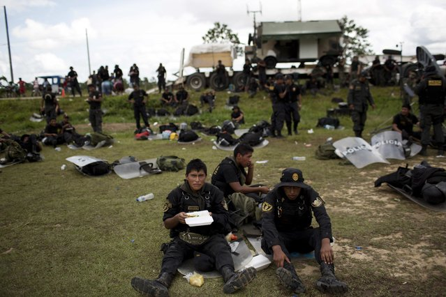 In this November 12, 2014 photo, policemen eat lunch at a makeshift base, after taking part in an operation to eradicate illegal gold mining camps in the area known as La Pampa, in Peru's Madre de Dios region. (Photo by Rodrigo Abd/AP Photo)