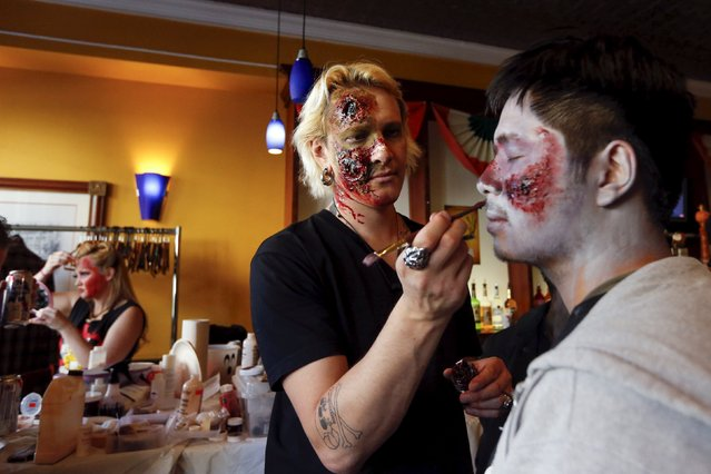 Mark Quinnette applies makeup on a man during the NYC Zombie Crawl in New York, October 18, 2015. (Photo by Shannon Stapleton/Reuters)