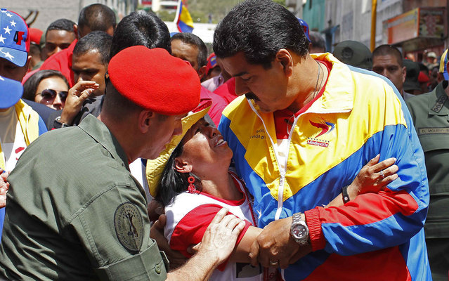 Venezuela's Vice President Nicolas Maduro consoles a supporter of deceased Venezuelan leader Hugo Chavez, as his coffin is driven through the streets of Caracas, March 6, 2013. Authorities have not yet said where the late Venezuelan President Chavez will be buried after his state funeral on Friday. (Photo by Carlos Garcia Rawlins/Reuters)