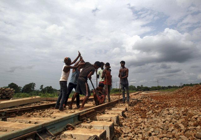 Labourers work at the installation site of a new railway track on the outskirts of Agartala, India, October 12, 2015. (Photo by Jayanta Dey/Reuters)