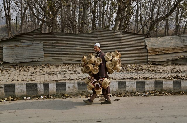 An elderly Kashmiri vendor sells Kangris or fire pots, on a cold morning in Srinagar, India, Monday, November 24, 2014. A kangri is an age-old device for keeping warm, consisting of a decoratively woven wicker case housing an earthen pot in which charcoal is burned. Many families make their living making and selling kangris, which cost from $3 to $32 each, depending on quality. Kashmiris usually buy a new one each year, and visitors also buy them as souvenirs, along with the samovar, a traditional Kashmiri tea pot. (Photo by Mukhtar Khan/AP Photo)