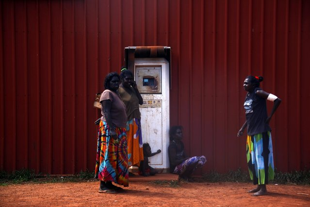 Members of the Australian Aboriginal community of Ramingining stand next to a machine used to pay for fuel in East Arnhem Land November 25, 2014. (Photo by David Gray/Reuters)