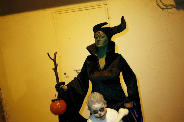 """A woman dressed as the character of Maleficent poses for a photo as she takes part in the second edition of """"Noche del Terror"""" (Horror night) during Halloween celebrations in the neighborhood of Churriana, near Malaga, southern Spain, October 31, 2015. (Photo by Jon Nazca/Reuters)"""