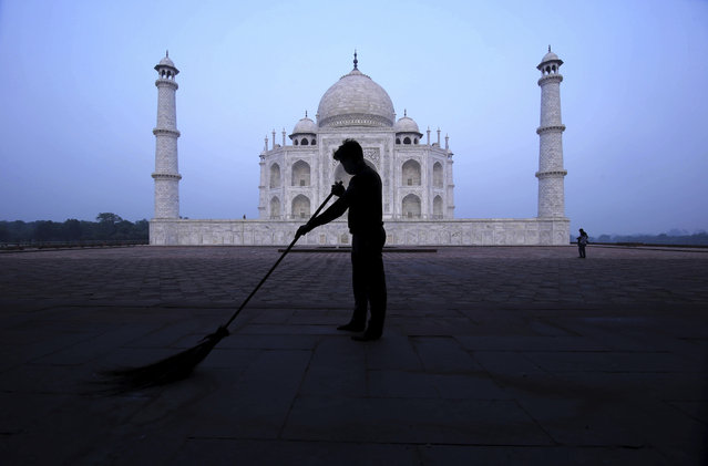A man sweeps at the Taj Mahal monument early morning in Agra, India, Monday, September 21, 2020. The Taj Mahal reopened Monday after being closed for more than six months due to the coronavirus pandemic. (Photo by Pawan Sharma/AP Photo)