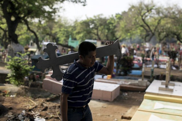 A man carries a cross for the grave of a relative during celebration of the Day of the Dead in Nahuizalco, El Salvador November 2, 2015. (Photo by Jose Cabezas/Reuters)