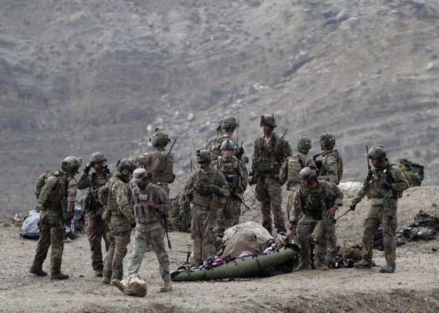 U.S. soldiers evacuate a dead body as they arrive to the scene after a NATO helicopter crashed in a field killing two American service members, near Gerakhel, eastern Afghanistan, Tuesday, April 9, 2013. The U.S.-led International Security Assistance Force said the cause of the crash is under investigation but initial reporting indicates there was no enemy activity in the area at the time. It did not immediately identify the nationalities of those killed. But a senior U.S. official confirmed they were Americans. (Photo by Rahmat Gul/AP Photo)