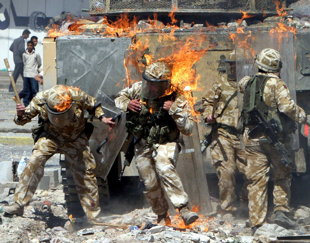 British troops covered in flames from a petrol bomb thrown during a violent protest by job seekers, who say they were promised employment in the security services, in the southern Iraq city of Basra, March 22, 2004. (Photo by Atef Hassan/Reuters)