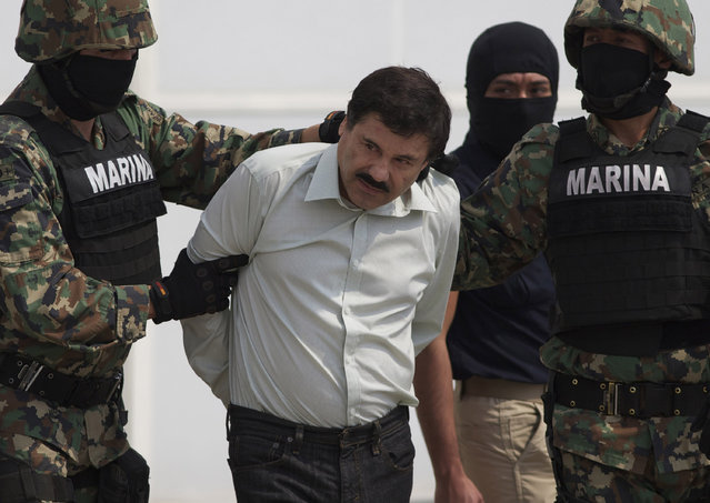 "In this February 22, 2014 file photo, Joaquin ""El Chapo"" Guzman is escorted to a helicopter in handcuffs by Mexican navy marines at a navy hanger in Mexico City, Mexico. Guzman, the head of Mexico's Sinaloa Cartel, was captured alive overnight in the beach resort town of Mazatlan. (Photo by Eduardo Verdugo/AP Photo)"