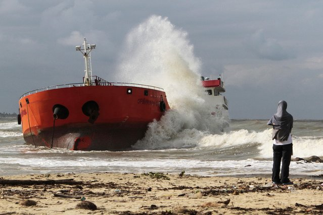 A girl looks from the beach as waves hit an Indonesian tanker that ran aground near Narathiwat in southern Thailand December 19, 2014. (Photo by Surapan Boonthanom/Reuters)