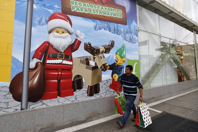 A man walks past a window display of Lego for Christmas at a Saga Falabella department store in the Miraflores district of Lima, December 23, 2014. (Photo by Mariana Bazo/Reuters)