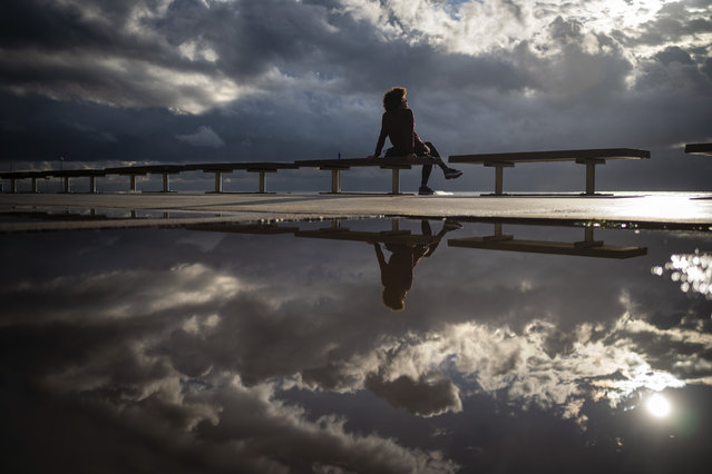 A woman sits in front of the sea after a storm in Barcelona, Spain, Wednesday October 14, 2020. Various regions in Spain, including northern Navarra and northeastern Catalonia, are either planning or implementing fresh restrictions against the spread of the new coronavirus. (Photo by Emilio Morenatti/AP Photo)