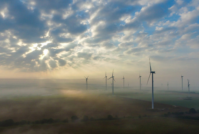 A picture taken with a drone shows the morning sun behind clouds over the mist enveloped landscape on a wind energy park near Sieversdorf in the district of Oder-Spree, Brandenburg, Germany, 10 September 2016. (Photo by Patrick Pleul/EPA)