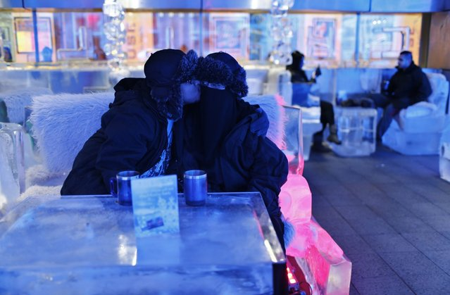 Honeymooner Ahmed, form Saudi Arabia who got married last week, kisses his veiled bride at Chillout cafe in Dubai May 12, 2013. Chillout, owned by UAE's Sharaf Group, is the first ice lounge in the Middle East, with temperatures set at –6 degrees Celsius (21 degrees Farenheit). The cafe, with its illuminated interiors, curtains, paintings and seating arrangements, is all made of carved ice and frozen sculptures. (Photo by Ahmed Jadallah/Reuters)