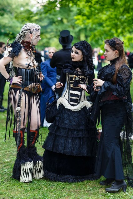 Three women in Victorian-style clothing chat during the traditional park picnic on the first day of the annual Wave-Gotik Treffen, or Wave and Goth Festival, on May 17, 2013 in Leipzig, Germany. The four-day festival, in which elaborate fashion is a must, brings together over 20,000 Wave, Goth and steam punk enthusiasts from all over the world for concerts, readings, films, a Middle Ages market and workshops. (Photo by Marco Prosch)