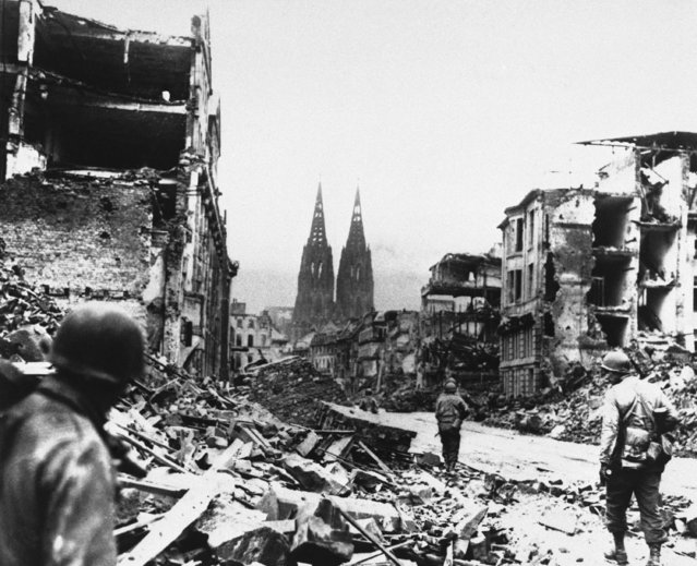 """Scene from """"The True Glory"""", General Dwight D. Eisenhower's film report of the conquest of Europe, distributed in this country by Columbia Pictures for the Office of the War Information through the War Activities committee. Troops of the 3rd Armored Division, U.S. First Army, advance through the ruins of Cologne, Germany. The twin spires of the famous cathedral, only five blocks sway, are undamaged, March 8, 1945. (Photo by AP Photo)"""