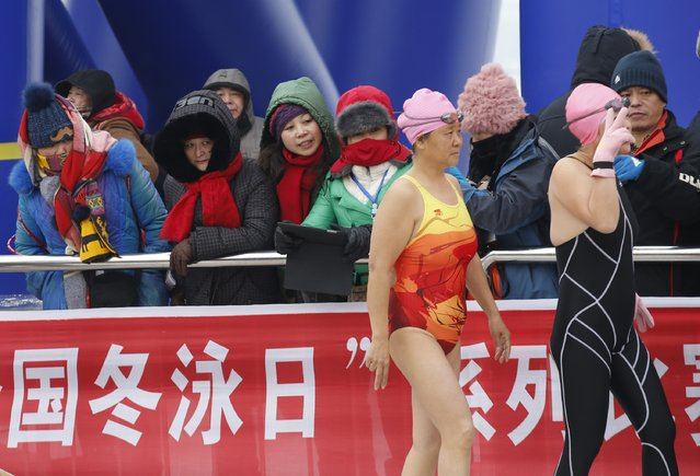 Spectators look at swimmers as they walk toward a starting line at a pool carved into thick ice covering the Songhua River during the Harbin Ice Swimming Competition in the northern city of Harbin, Heilongjiang province January 5, 2015. (Photo by Kim Kyung-Hoon/Reuters)