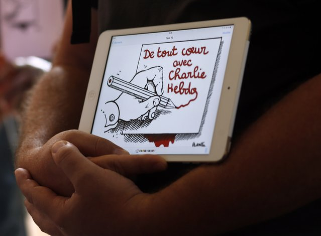 "A man holds up a tablet with an image that reads ""wholeheartedly with Charlie Hebdo"" during a tribute to the victims of a shooting by gunmen at the offices of weekly satirical magazine Charlie Hebdo in Paris, at France's Embassy in Buenos Aires January 7, 2015. (Photo by Marcos Brindicci/Reuters)"