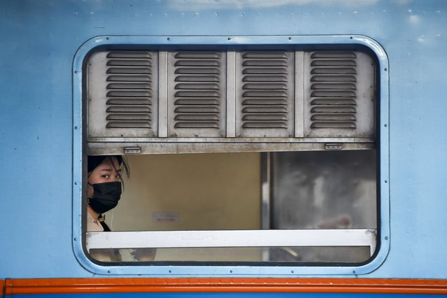 A woman wearing a protective mask sits in a train before its departure at the Bangkok Railway Station in Bangkok, Thailand, 30 December 2020. The government announced that there won't be travel restrictions for the New Year period, although recommended people to choose to remain home if possible in order to help contain the spread of the coronavirus disease (COVID-19) pandemic. From 15 to 30 December the government has found COVID-19 infections in 48 provinces, according to the center for COVID-19 Situation Administration. (Photo by Diego Azubel/EPA/EFE)