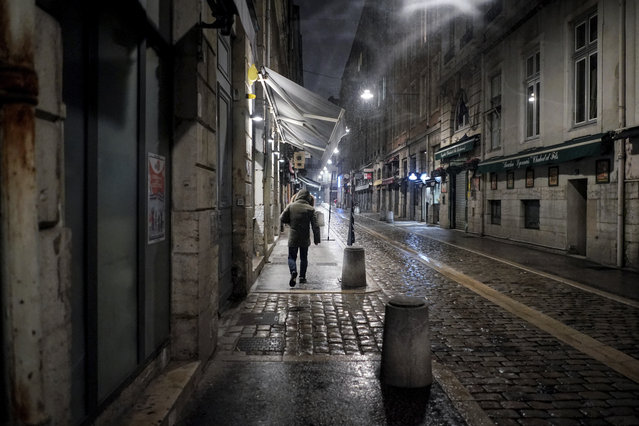 A man walks in the street at the start of the new curfew to counter the COVID-19 in the center of Lyon, central France, Saturday, January 16, 2021. All of France will be under a stricter curfew starting Saturday at 6 p.m. for at least 15 days to fight the spread of the coronavirus. (Photo by Laurent Cipriani/AP Photo)