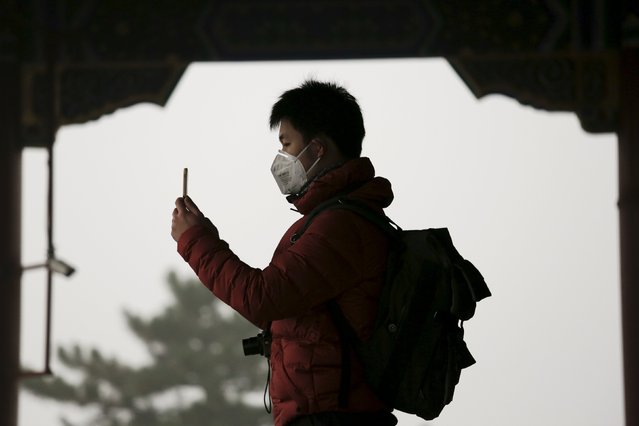 A man wearing protective mask takes pictures of the Forbidden City from the top of Jingshan Park on an extremely polluted day as hazardous, choking smog continues to blanket Beijing, China December 1, 2015. (Photo by Damir Sagolj/Reuters)