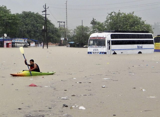 A man rows past a bus partly submerged in flood water in Rishikesh, in the northern Indian state of Uttarakhand, India, Tuesday, June 18, 2013. Monsoon torrential rains have cause havoc in northern India leading to flash floods, cloudbursts and landslides as the death toll continues to climb and more than 1,000 pilgrims bound for Himalayan shrines remain stranded. (Photo by AP Photo)